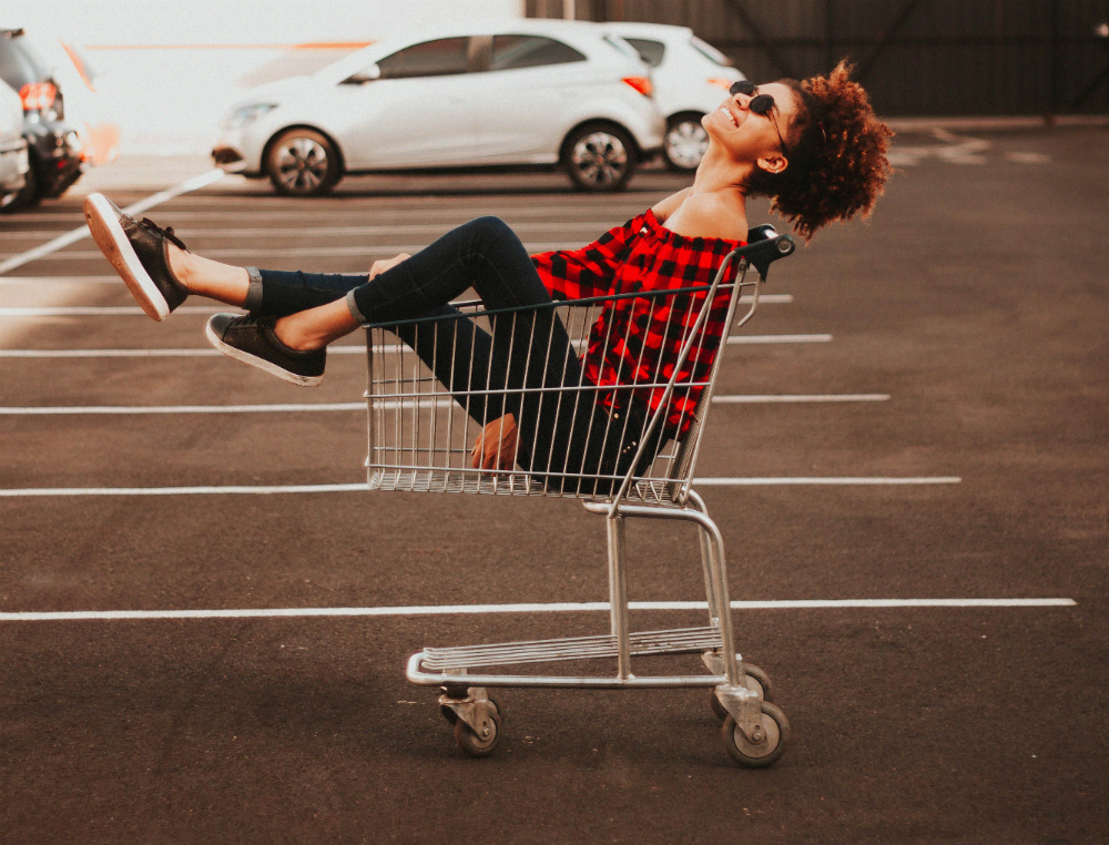 A woman sitting in shopping cart looking happy.