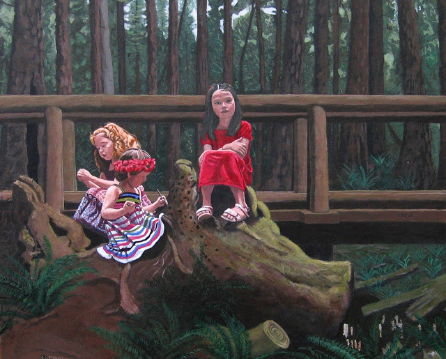 Three young girls sitting on a fallen tree with the forest behind them.